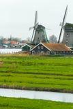 Moulins à vent néerlandais traditionnels et vieille maison de ferme sur la berge Images stock