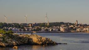 Moulins à vent près de l'océan et de la ville Images stock