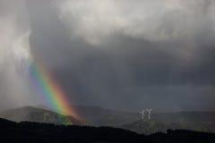 Moulins d'énergie éolienne d'arc-en-ciel et dans la forêt noire Photographie stock libre de droits