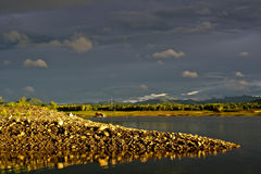 Mound on lakeside and dark sky after rain Royalty Free Stock Photography