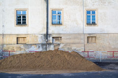 Mound on the street. Street with facade of the building. Heap of grit and gravel on the street Stock Images
