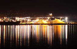 Mounds of Sulfur at Night. Sulfur Piles & lights reflecting in the water at night at a shipyard in Vancouver, British Columbia Stock Image