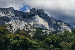 Mount Ai-Petri rises above the forest and the stone tower. Russia, the Crimea stock photos