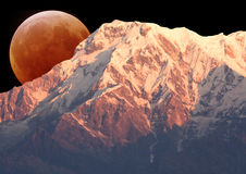Mount Annapurna South and the Moon. Image of Mount Annapurna South on the Dhaulagiri-Annapurna-Manaslu Himalayan Mountain Range, Nepal, against a backdrop of a royalty free stock photo