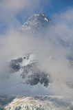 Mount Assiniboine and clouds. Mount Assinboine summit and glacier surrounded by misty morning clouds Royalty Free Stock Photography
