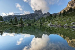 Mount Averau reflected in lake Limedes at sunrise, blue sky with clouds, Dolomites, Veneto, Italy stock photography
