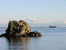Mount Baker Ocean View with Freighter West. A container ship photographed from the Gulf Islands in British Columbia, Canada. This freighter is travelling through Stock Photography