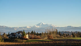 Mount Baker Viewed from the Fraser Valley. Mount Baker, a dormant volcano, in Washinton state viewed from the Fraser Valley in British Columbia with a mansion in Stock Photography