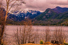 Mount Baldy From Point Park. On the shore of a lake, peeking through trees, a snow capped mountain in the distance royalty free stock images