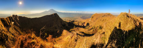 Mount Batur sunrise panorama. Beautiful 180 degree panorama at sunrise on top of Mount Batur on the island of Bali, Indonesia, with a beautiful tourist looking Stock Photo