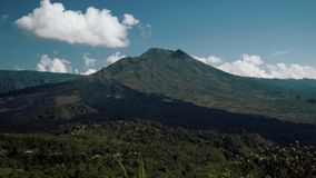 Mount Batur volcano view on sunny summer day in Bali, Indonesia. Mount Batur volcano view from Kintamani on sunny summer day with blue sky and small clouds in stock video footage