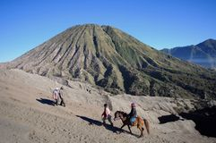 MOUNT BROMO, JAVA INDONESIA - JUNE 28, 2014: Undefined model posing on a horse under the Bromo massif. Royalty Free Stock Photo