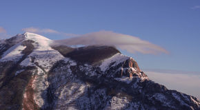 Mount Catria with snow in winter at sunset, blue sky with clouds. Umbria, Italy Royalty Free Stock Photo