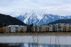 Mount Cheam Provides a Striking Backdrop. The snow capped peaks of Mount Cheam provide a striking backdrop for the scenic resort town of Harrison Hot Springs in Royalty Free Stock Photo