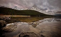Mount Chephren and Waterfowl lake in autumn. Perfect reflection in calm water of lake. Dramatic clouds. Canadian Rockies. Banff National Park. Alberta. Canada royalty free stock images