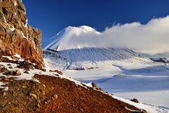 Mount Doom in the snow, winter landscape in Tongariro national park. Tongariro national park in winter weather. Sunny winter day, snow and ice covers the peak of stock images