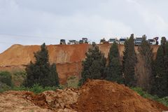 Mount of earth in a construction site with trucks and tractors parting atop. Royalty Free Stock Photos