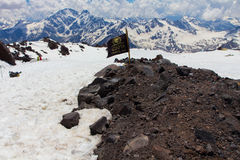 2014 07 Mount Elbrus, Russia: Man is sleeping on the slope of Mount Elbrus near the flag Stock Images