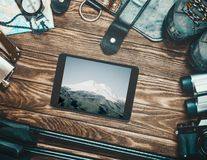 Mount Elbrus on screen of tablet and travel equipment. stock photography