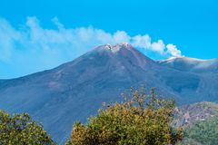 Mount Etna, Sicily. View of the Sicilian Volcano,Mount Etna. Vista of summit craters and strong fumarole activity producing a steam plume, on a bright sunny day royalty free stock photo