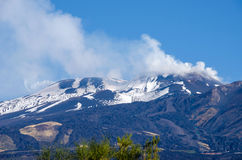 Mount Etna with the smoking peak. Mount Etna, an active stratovolcano, from the south with the smoking peak in the upper left, snowy flanks and cable car line in stock photos