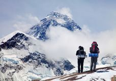 Mount Everest from Kala Patthar with two tourists. Panoramic view of Mount Everest from Kala Patthar with two tourists on the way to Everest base camp Stock Photo