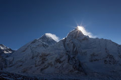 Mount Everest Peak (Sagarmatha, Chomolungma). First rays of the sun coming up behind the Nuptse mountain. Sunrise over the summit of the mount Everest royalty free stock images