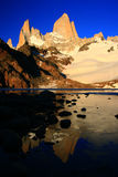 Mount Fitz Roy Argentina at sunrise. The Fitz Roy Range and clear blue sky reflecting in the semi-frozen lake of the three (lago de los tres) at sunrise Stock Image