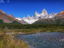A fast flowing stream fed from a Patagonian glacier. Mount Fitz Roy and surrounding peaks near El Chalten Santa Cruz Argentina Royalty Free Stock Images