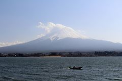 Mount Fuji as seen from Lake Kawaguchi. People are doing sport and taking photos, meanwhile. Taken in Yamanashi, Japan - February 2018 royalty free stock photo