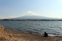 Mount Fuji as seen from Lake Kawaguchi. People are doing sport and taking photos, meanwhile. Taken in Yamanashi, Japan - February 2018 royalty free stock photos