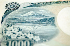 Mount Fuji banknote. Detail of a 1000 Yen banknote with the Japanese landmark Mount Fuji on the reverse.  Used banknote photographed at an angle Stock Photography