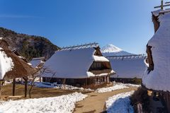 Mount Fuji on a clear winter day, between traditional japanese thatched houses in Iyashino-Sato Nenba traditional village, in the. Mount Fuji on a clear winter royalty free stock photo