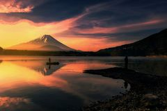 Mount Fuji at dawn, Shoji lake, Japan. Silhouette landscape of fisherman on boat and edge at Shoji lake with mt. Fuji view reflection at dawn with twilight sky Stock Images