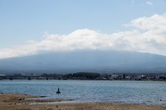 Mount Fuji that is the famous landmark in Japan. With white cloud and lake as foreground on blue sky background royalty free stock image