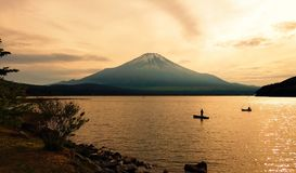 Recreational anglers silhouette fishing in front of Mount Fuji at dusk. Mount Fuji in Japan looking majestic above Lake Yamanakako while two fishermen in small Stock Image