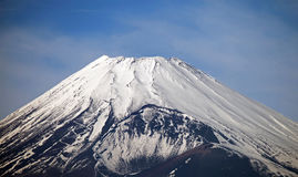 MOUNT FUJI, JAPAN. Snow capped summit of mount Fuji in early December. A zig zag road leading to the highest drivable point can be seen on the left side and Stock Photo