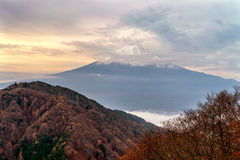 Mount Fuji in the mist. Beautiful mount Fuji in the mist with autumn colour season of trees. The Kawaguchi town and lake below covered with the fog royalty free stock photo