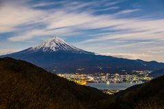 Mount Fuji, or Fuji San in Japanese, famous mountain in Japan standing tall against cloudy blue sky at night towering the. Kawaguchigo town and lake in the stock image