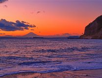 Mount Fuji at sunset with coastline and beach. Mount Fuji as seen from the Chiba coastline in Japan at sunset with soft waves and sand in foreground and oranges Royalty Free Stock Photography