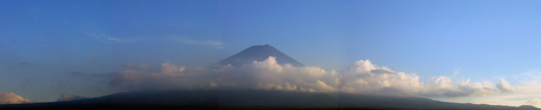 Mount Fuji surrounded by clouds - panorama. Majestic mount Fuji in the light of the sunset, surrounded by clouds. Panoramic view Royalty Free Stock Images