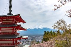 Mount Fuji viewed from behind Chureito Pagoda in full bloom cherry blossoms. Springtime sunny day in clear blue sky natural background. Arakurayama Sengen Park royalty free stock images