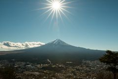 Mount Fuji in winter season with sun like a star by narrow f stop. Mount Fuji in winter season; the nice sky at Kawaguchiko royalty free stock photo