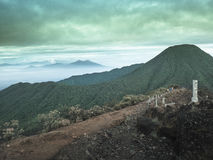 Mount Gede. Or Gunung Gede is a stratovolcano in West Java, Indonesia. The volcano contains two peaks with  as one peak and Mount Pangrango for the other one Stock Photos