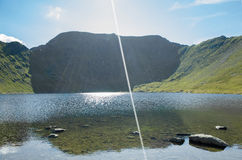 Mount Helvellyn, 950 metres high above Lake Ullswater. Above the red tarn, the summit of mount Helvellyn, 950 metres high above Lake Ullswater, Lake District Stock Photos