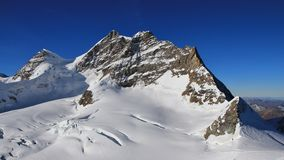 Peak of mount Jungfrau and glacier with large crevasses. Stock Images