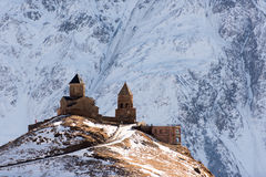 Mount Kazbeg and the Caucasus. Snow covered Caucasus landscape with dominant mount Kazbeg in Georgia, Europe near the town of Stepantsminda, and trinity church Royalty Free Stock Photo