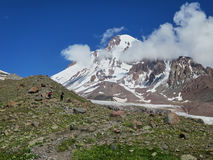 MOUNT KAZBEK, GEORGIA - AUGUST 2, 2016: Climbers on the way up to Mt. Kazbek. Stock Photos