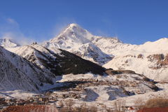 The Mount Kazbek and Gergeti village - the view from Stephantsminda, Georgia. Mount Kazbek (Mkinvartsveri) is a dormant stratovolcano and one of the major Stock Images