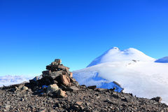 Mount Kazbek. Stone cairn at the mountain top on the background of mount Kazbek Royalty Free Stock Images